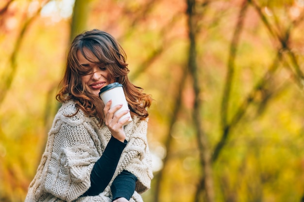 Pretty girl with a cup of hot drink smiles in the forest in the autumn.