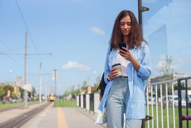 一杯のコーヒーとかわいい女の子は、朝のバスまたは路面電車の路面電車を待ちます。アプリを通じてトランスポートを監視するスマートフォンを持つ若い女性。