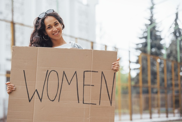 Pretty girl with curly hair stands with handmade feminist poster in hands