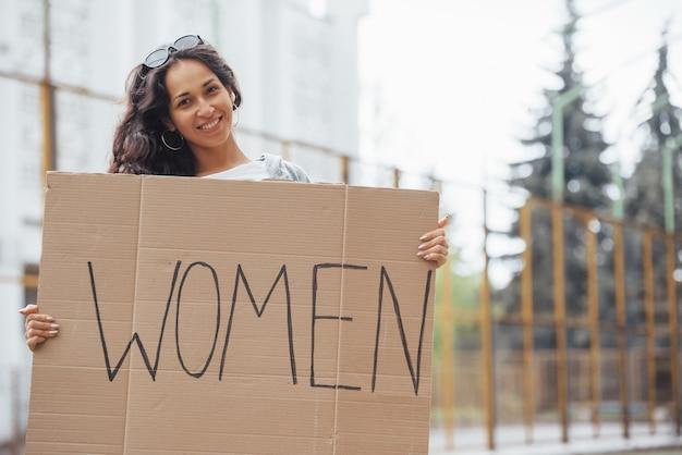 Красивая девушка с вьющимися волосами стоит с феминистским плакатом ручной работы в руках