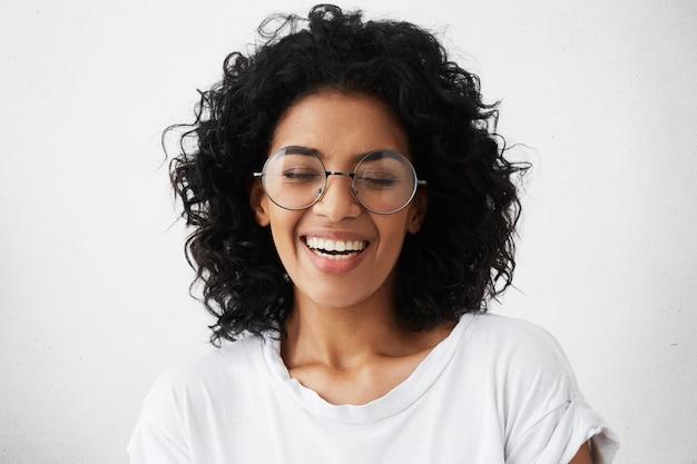 Красивая девушка с темной чистой кожей и красивой зубастой улыбкой громко смеется над смешной шуткой