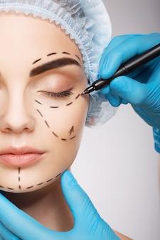 Красивая девушка с темными бровями в синей медицинской шляпе на фоне студии, руки врача в синих перчатках, рисуя линии перфорации на лице, концепция пластической хирургии.