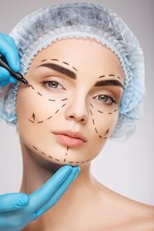 Красивая девушка с темными бровями в синей медицинской шляпе на стене, руки врача в синих перчатках, рисующих линии перфорации на лице, концепция пластической хирургии.