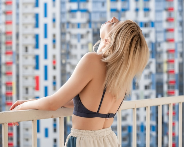 Pretty girl with freckles in a purple lace top and sweatpants stands on the balcony