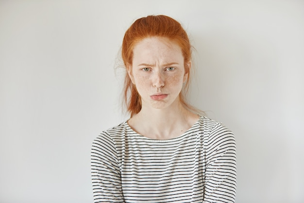 Pretty girl with ginger hair, gathered in ponytail pouting her lips, looking with irritated and offended face expression while standing isolated