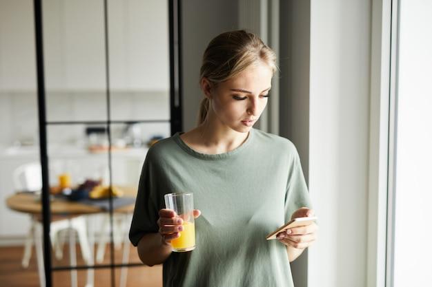 Красивая девушка с стакан апельсинового сока, наблюдая за любопытных сотрудников в смартфоне