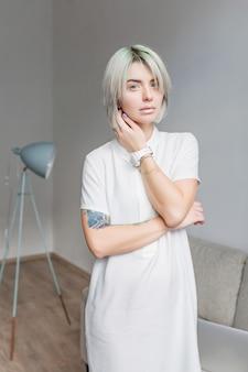 灰色の短い髪型のかわいい女の子は、灰色のスタジオでカメラにポーズをとっています。彼女は白いドレスと軽い化粧を着ています。