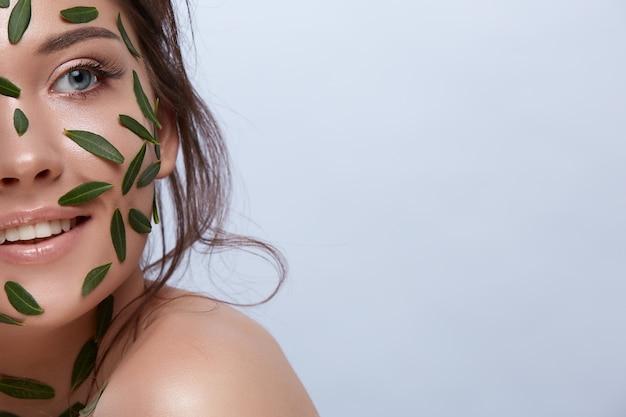 회색에 고립 된 측면을 찾고 그녀의 얼굴에 녹색 잎 예쁜 여자