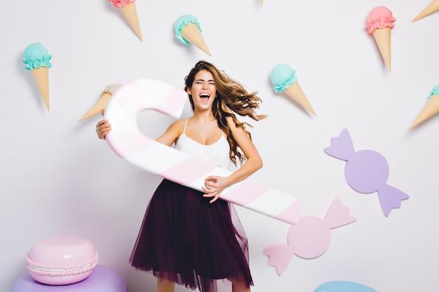 Красивая девушка с развевающимися волосами в фиолетовой юбке поет любимую песню и держит игрушечный леденец. портрет стильной молодой женщины с закрытыми глазами, весело на вечеринке и танцах.