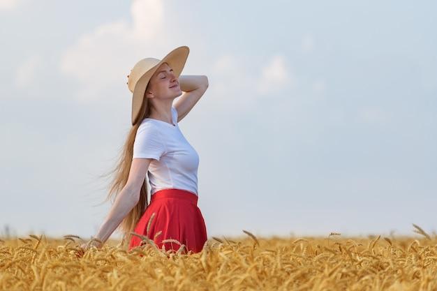 Красивая девушка в шляпе прогулки в пшеничном поле и наслаждаясь солнечный день.