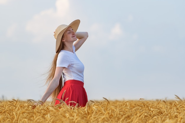 Pretty girl with hat walks in wheat field and enjoying sunny day.
