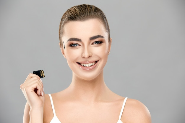 Pretty girl with her hair tightened and perfect smile holding memory card , female and technology