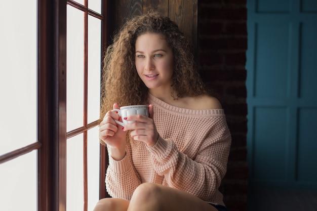 창턱에 앉아 긴 컬링 머리를 가진 예쁜 소녀. 그녀의 손에 흰색 컵을 들고 소녀.