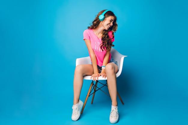 Красивая девушка с длинными вьющимися волосами охлаждает в кресле на синем фоне. на ней шорты, розовая футболка, белые кроссовки. она слушает музыку в синих наушниках.