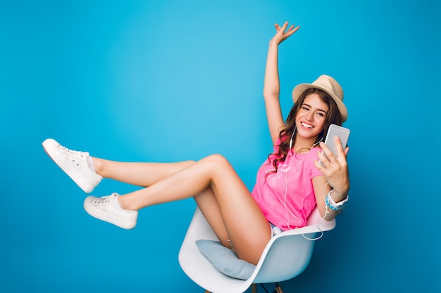 Pretty girl with long curly hair in hat chilling in chair on blue background in studio. she wears shorts, pink t-shirt, white sneakers. she holds legs above and makes selfie-portrait.