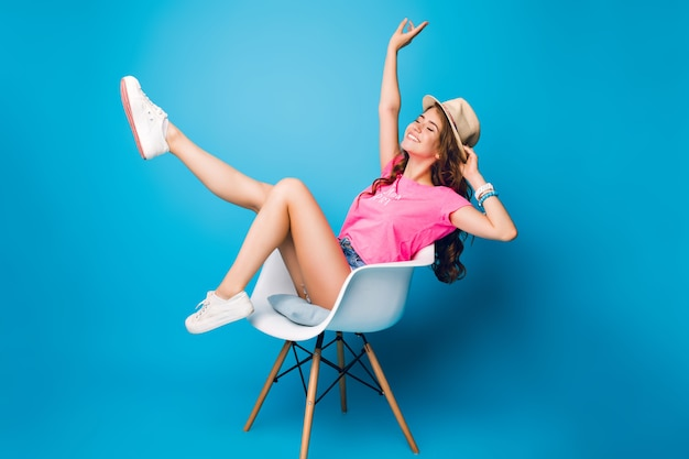 Pretty girl with long curly hair in hat is chilling in chair on blue background in studio. she wears shorts, pink t-shirt, white sneakers. she keeps legs above and looks excited.