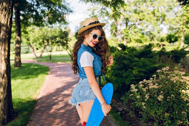 帽子とサングラスで長い巻き毛を持つかわいい女の子は、夏の公園でスケートボードで歩いています。彼女はジーンズのジャーキン、ショートパンツを着ています。彼女は赤い唇で笑っています。