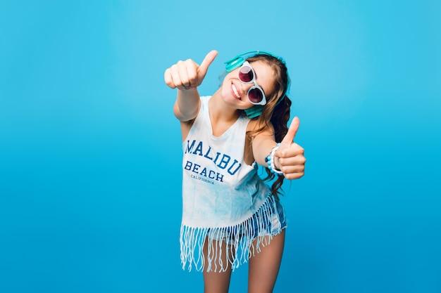 Красивая девушка с длинными вьющимися волосами в хвосте в синих очках на синем фоне в студии. она носит белую футболку, шорты и слушает музыку в синих наушниках, выглядит довольной и счастливой.