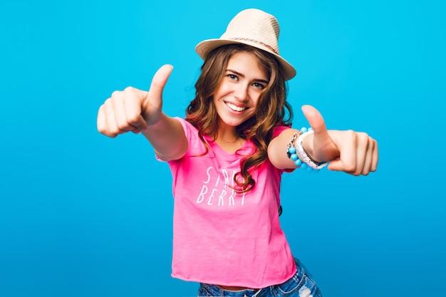 Красивая девушка с длинными вьющимися волосами, позирует на синем фоне в студии. она носит розовую футболку и шляпу. она показывает руки на камеру и выглядит счастливой.