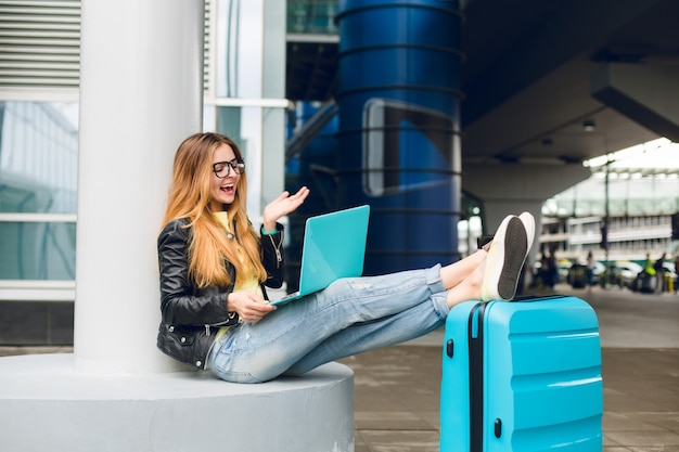 Pretty girl with long hair in black glasses is sitting outside in airport. she wears jeans, black jacket, jellow shoes. she put her legs on suitcase and speaking on laptop. she looks happy.