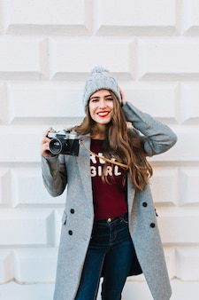 Pretty girl with long hair in grey coat on  wall  outdoor. she holds camera, touches knitted hat and smiling.