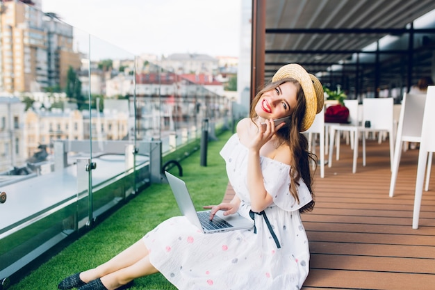 Pretty girl with long hair in hat is sitting on floor on the terrace. she wears a white dress with naked shoulders. she is typing on  laptop and speaking on phone.