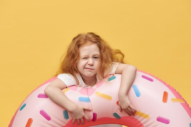 Красивая девушка с длинными волосами обнимает надувной плавательный круг и морщится