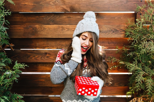 Красивая девушка с длинными волосами в зимней одежде на деревянном. она держит рождественский подарок и выглядит удивленной.