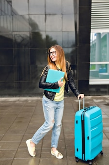 Pretty girl with long hair is walking with suitcase outside in airport. she wears black jacket with jeans and holds laptop. she looks happy.