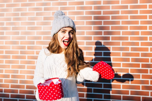Pretty girl with long hair in knitted hat and gloves with open present on wall  outside. she looks astonished .