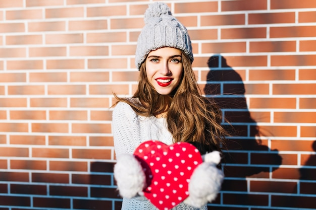 Pretty girl with long hair in knitted hat, warm sweater on wall  outside. she holds red heart in gloves, smiling .