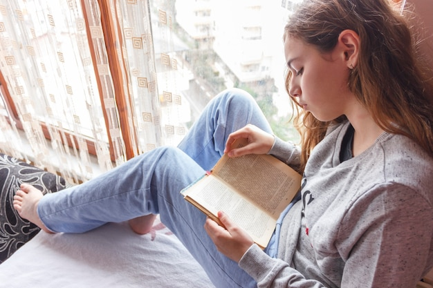 Pretty girl with long hair reading a book near window