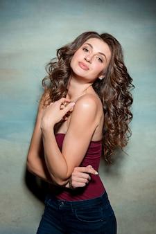 Красивая девушка с длинными волосами улыбается и наслаждается жизнью