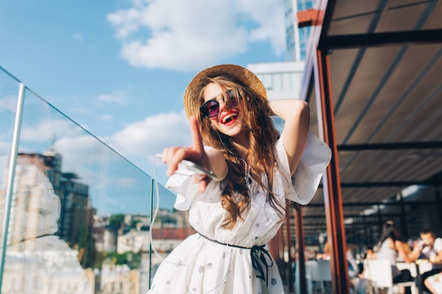 Pretty girl with long hair  in sunglasses is listening to music  on the terrace. she wears a white dress, red lipstick and hat . she is stretching hand to the camera and dancing. buttom view.