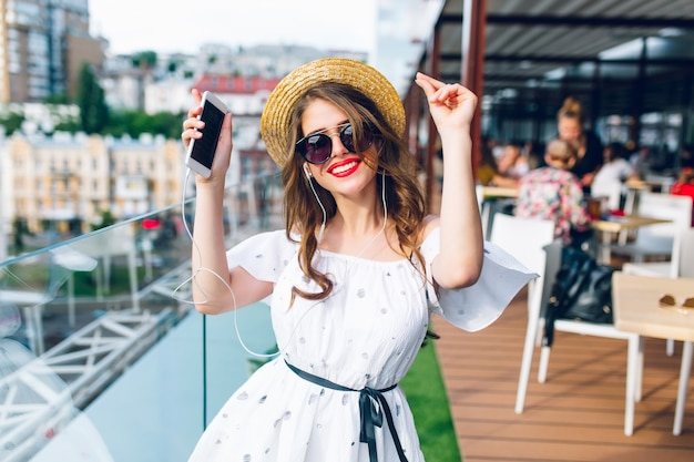 Pretty girl with long hair  in sunglasses is listening to music through headphones on the terrace. she wears a white dress with bare shoulders, red lipstick  and hat . she is dancing.