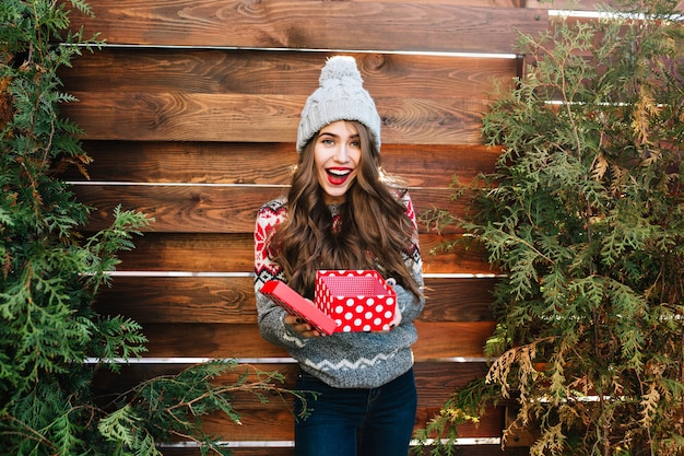 Pretty girl with long hair with christmas box on wooden . she wears warm winter clothes, knitted hat, smiling happy .