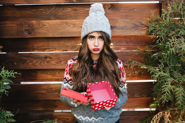 Красивая девушка с длинными волосами с пустой рождественской коробкой на деревянном. в теплой зимней одежде, выглядит недовольной.