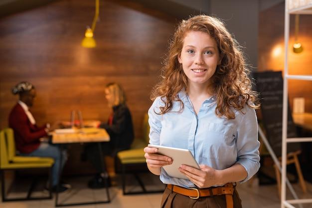 Красивая девушка с длинными волнистыми волосами смотрит на вас во время использования планшета с двумя коллегами