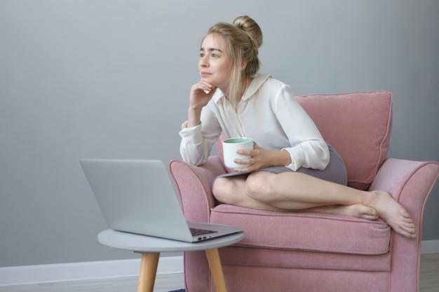 Bella ragazza con l'acconciatura disordinata con un'espressione facciale sognante, gustando un caffè, seduto in una comoda poltrona davanti al computer portatile aperto, pensando ai piani futuri e alle vacanze estive