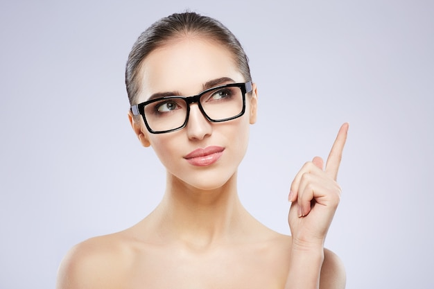 Pretty girl with nude make up posing at grey studio background, beauty photo concept, perfect skin, wearing glasses, vision concept, thinking.