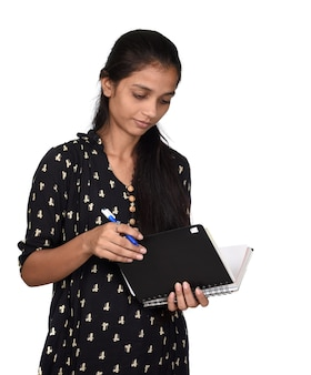 Pretty girl with pen and notebook on white background. thinking plans for nearest future.