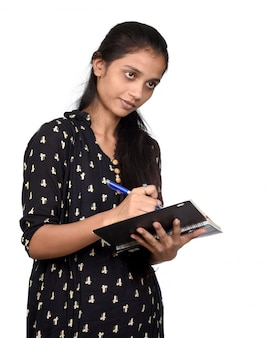 Pretty girl with pen and notebook on white space. thinking plans for nearest future.