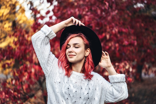 Pretty girl with red hair and hat walking in the park, autumn time.