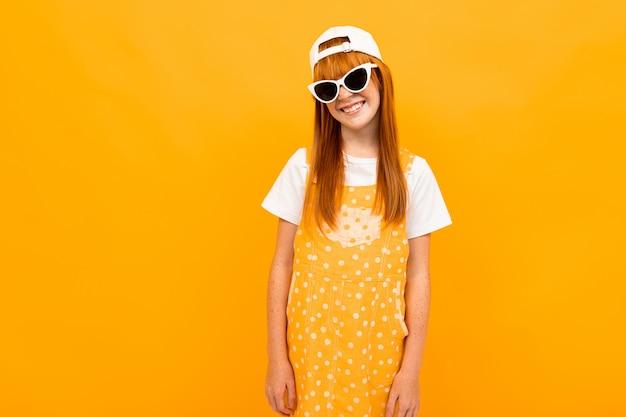 カメラにポーズをとって赤い髪と黄色の背景に分離されたサングラスをかけた笑顔でかわいい女の子