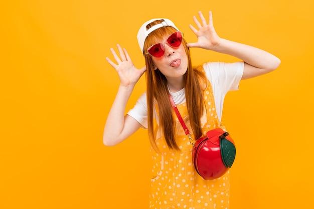黄色の背景に分離された小さなリンゴのバッグとカメラの笑顔でポーズをとって赤い髪のかわいい女の子。