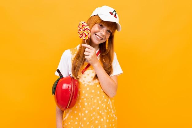小さなアップルバッグとカメラにポーズをとって赤い髪のかわいい女の子は、黄色の背景に分離されたロリポップを食べる