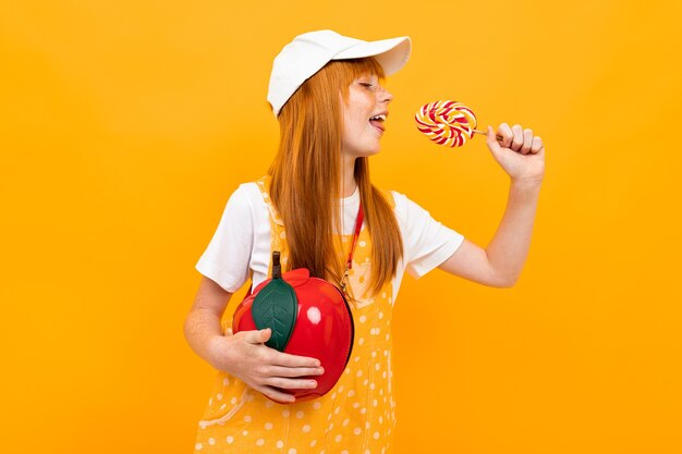 小さなリンゴの袋とカメラでポーズをとって赤い髪のかわいい女の子は黄色の背景で隔離のロリポップを食べる