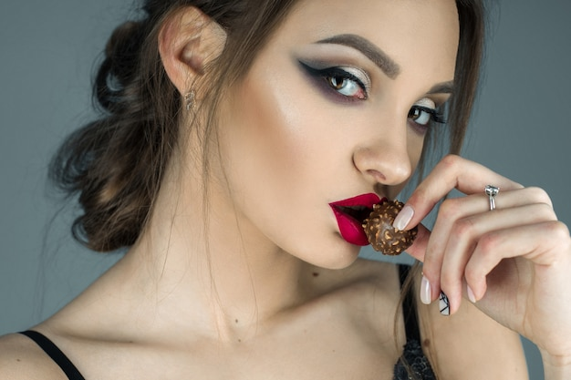 Pretty girl with red lips eats chocolate candy and looking at the camera in studio