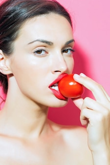 Pretty girl with red tomato