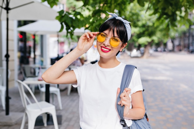Pretty girl with short black hair smiling and holding blue backpack on one shoulder while posing on the street in morning